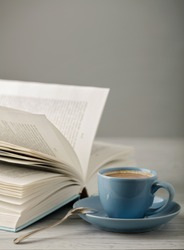 Coffee in a light blue cup and book in blue cover on a wooden background. Selective focus.