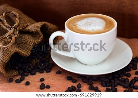 Coffee in a white cup and coffee beans on the table.