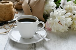 Coffee in a white cup and saucer next to a bouquet of white peonies peony flowers from the garden tied up in brown paper wrapping with twine. light bright airy lifestyle