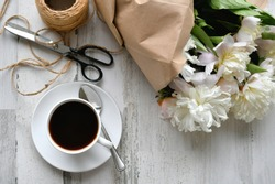 Coffee in a white cup and saucer with French macarons next to a bouquet of white peonies peony flowers from the garden tied up in brown paper wrapping with twine. light bright airy lifestyle