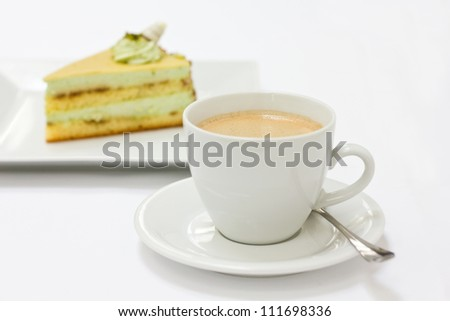 Coffee in a white cup with a spoon and a slice of cake slightly blurry in the background