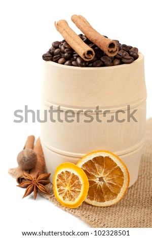 Coffee in a wooden barrel and spices: cinnamon, star anise and dried orange