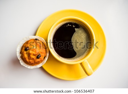 Coffee in an yellow cup and a muffin