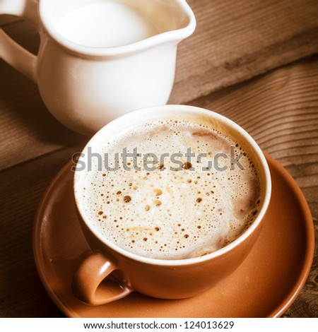 Coffee in brown cup and milk on wood background closeup