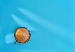 Coffee in glass cup is positioned against a bright blue background, shadows from leaves on the table. Strong espresso with aromatic crema, copy space layout. Banner with coffee for breakfast