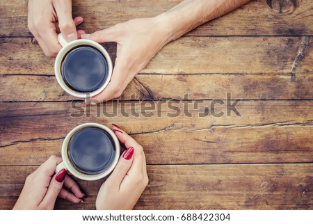 Coffee in hand. The lovers are together. Selective focus.