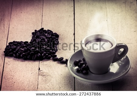 Coffee in love,coffee in cup with roasted coffee bean heart shape on wooden background in sweet color filterd