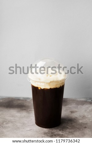 Coffee in plastic takeaway cup with cream on gray background #1179736342