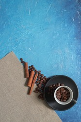 coffee in the cup on blue background with coffee beans