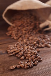 Coffee is poured from a burlap on a wooden background, stilllife