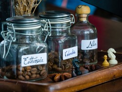 Coffee jars in coffee shop for customer to smell coffee beans from different origins before order. There are coffee beans from Ethiopia, Columbia and Nan. Nan is the province in Thailand.