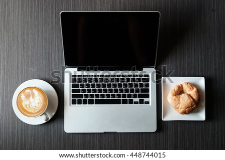 coffee, laptop and croissants to show a business breakfast on the back desk in morning #448744015
