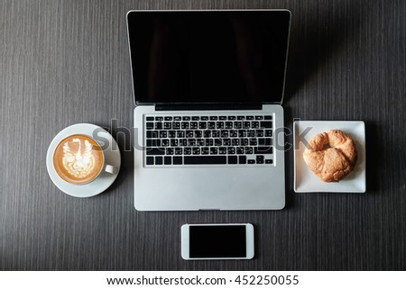 coffee, laptop, smart phone and croissants to show a business breakfast on the back desk in morning #452250055