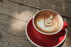 Coffee latte art in a red cup on wood table background