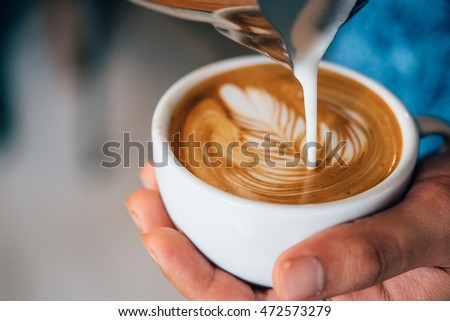 coffee latte art make by barista in coffee shop cafe vintage color tone