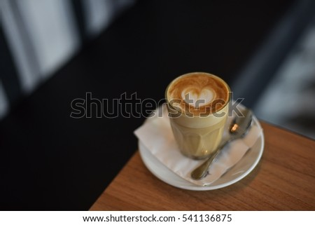 coffee latte art on the wooden desk in coffee shop vintage color tone #541136875