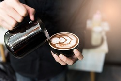 Coffee Latte Barista making pattern in a cup of coffee shop