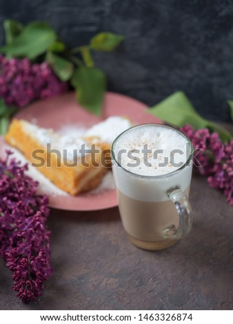 Coffee latte in a glass glass glass glass with a piece of cake cozy atmospheric background with flowers #1463326874
