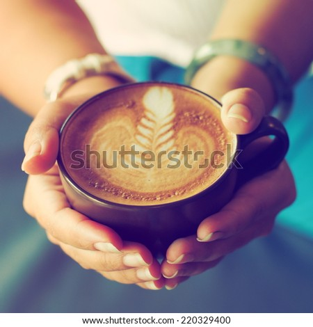 Coffee latte with hand in vintage color tone style #220329400