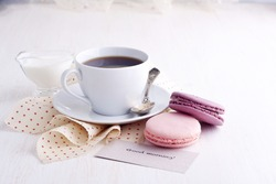 Coffee, macaroons and cream with a good morning card on a white table