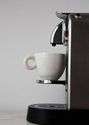 Coffee Machine and Empty Cup Ready for Pouring Beverage on White Wall Background