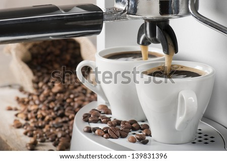 coffee machine makes two coffee with coffee beans on background