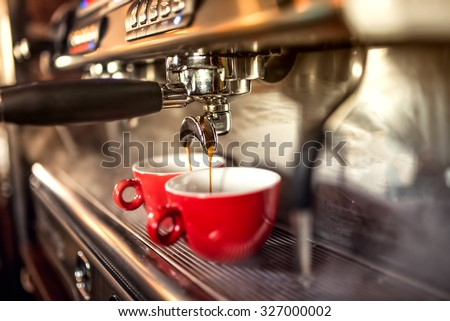 coffee machine preparing fresh coffee and pouring into red cups at restaurant, bar or pub. Stok fotoğraf ©