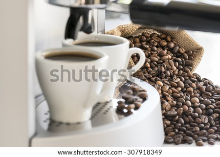 coffee machine with two coffee cups and coffee beans, focus on coffee beans