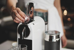coffee machine,women holding coffee capsules and put in espresso machine with empty cup of coffee at kitchen .