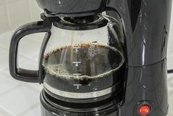 Coffee maker pot filling close up.