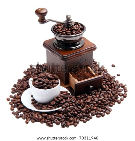 Coffee mill and cup with coffee beans over white background