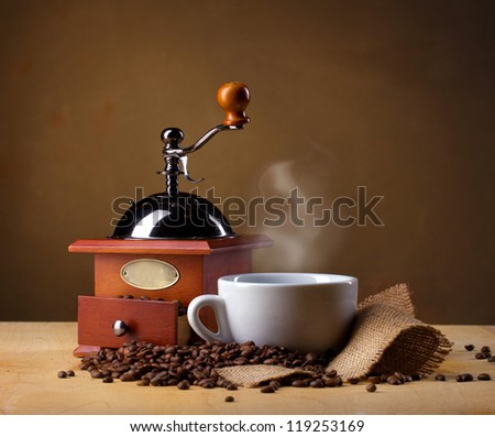 coffee mill, coffee cup and coffee beans on brown background