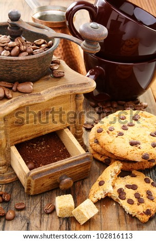 Coffee Mill, cups and biscuits on a wooden table.
