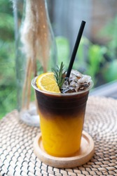 Coffee mix with orange juice and cold brew Fusion coffee on the wooden table in cafe, focus one point