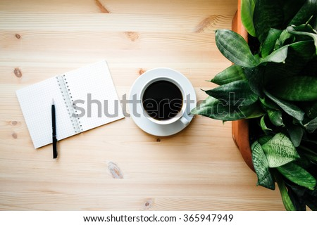 coffee mug and a blank Notepad with pen and house plant #365947949