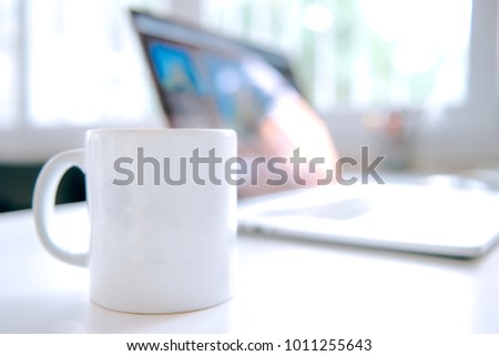 Coffee mug and laptop in office table interior #1011255643
