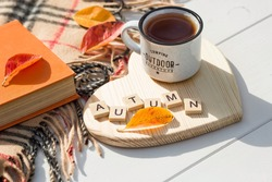 Coffee mug and wooden letters on a wooden stand in the shape of a heart on a white table. The concept of the fall season. A Cup of tea with autumn leaves. fall time. Copy space.