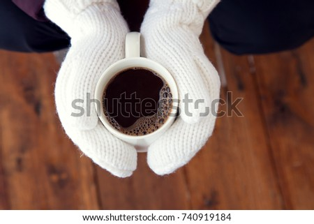 coffee mug in hands mittens outdoor in the winter on Christmas Eve #740919184