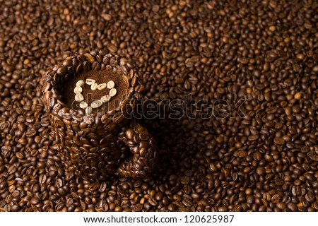 Coffee mug made of coffe beans standing on the surface of coffee, filled with raw, heart shaped coffee beans