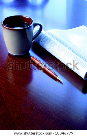coffee mug magazine and pen on wood desk with blue tone - stock photo