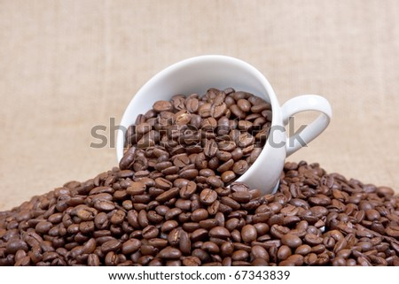 Coffee mug over the raw beans