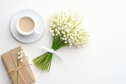 Coffee mug with bouquet of flowers lily of the valley and gift box on white background. Flat lay, top view, copy space.