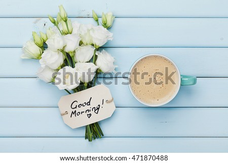 Coffee mug with white flowers and notes good morning on blue rustic table from above. Beautiful breakfast. Flat lay.