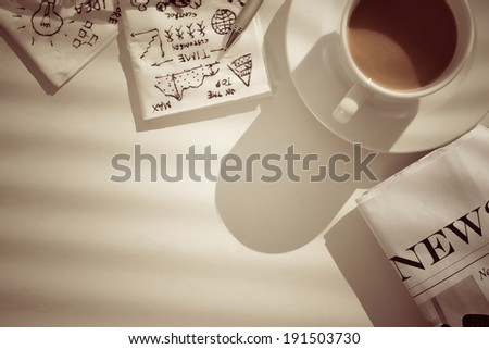 Coffee, newspaper and napkins with pictures, showing business breakfast