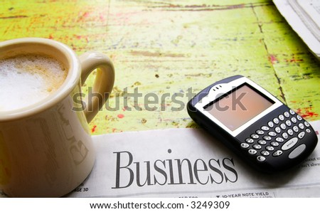 Coffee, newspaper business section and pda device