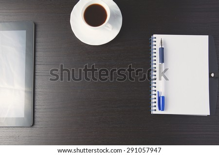 coffee notepad pen and tablet on dark wood workspace. Top view.