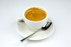 coffee on a white plate with a spoon on a white background