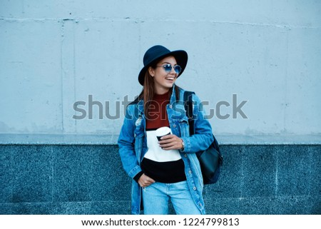 Coffee on the go. Beautiful young woman holding coffee cup and smiling while walking along the street.Copy space with urban grey wall.Fashionable portrait of smiling elegant brunette girl