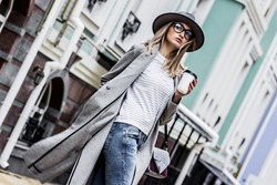 Coffee on the go. Stylish and young woman in coat and hat drinking coffee outdoors. Beautiful hipster girl in modern urban outfit walking city streets with paper cup of coffee. City fashion concept