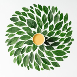 Coffee or tea cup on green leaves background Flat lay.